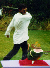 Rev. DeLuxe hacks a watermelon with a machete during a sacrifice in 1993